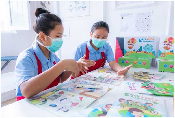 two maids undergoing a training by reading books